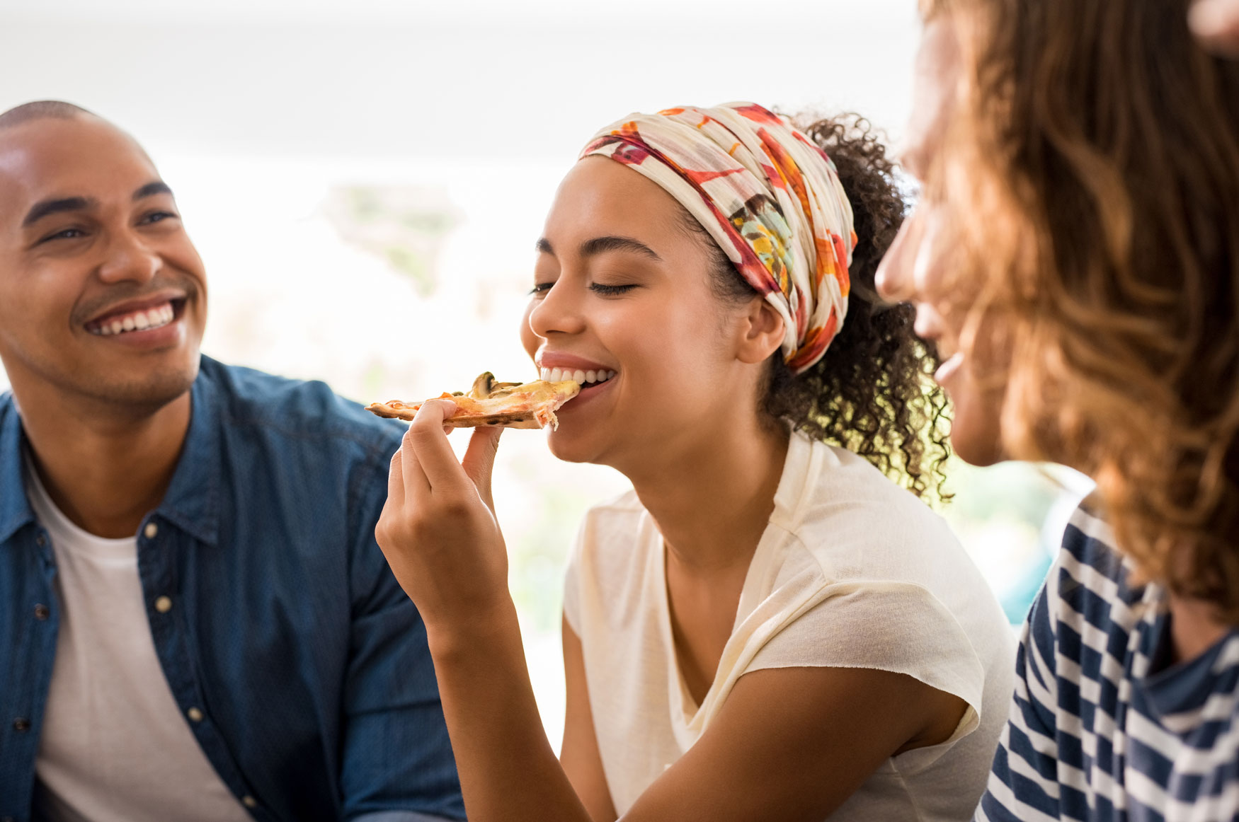 Group of people eating pizza and laughing.