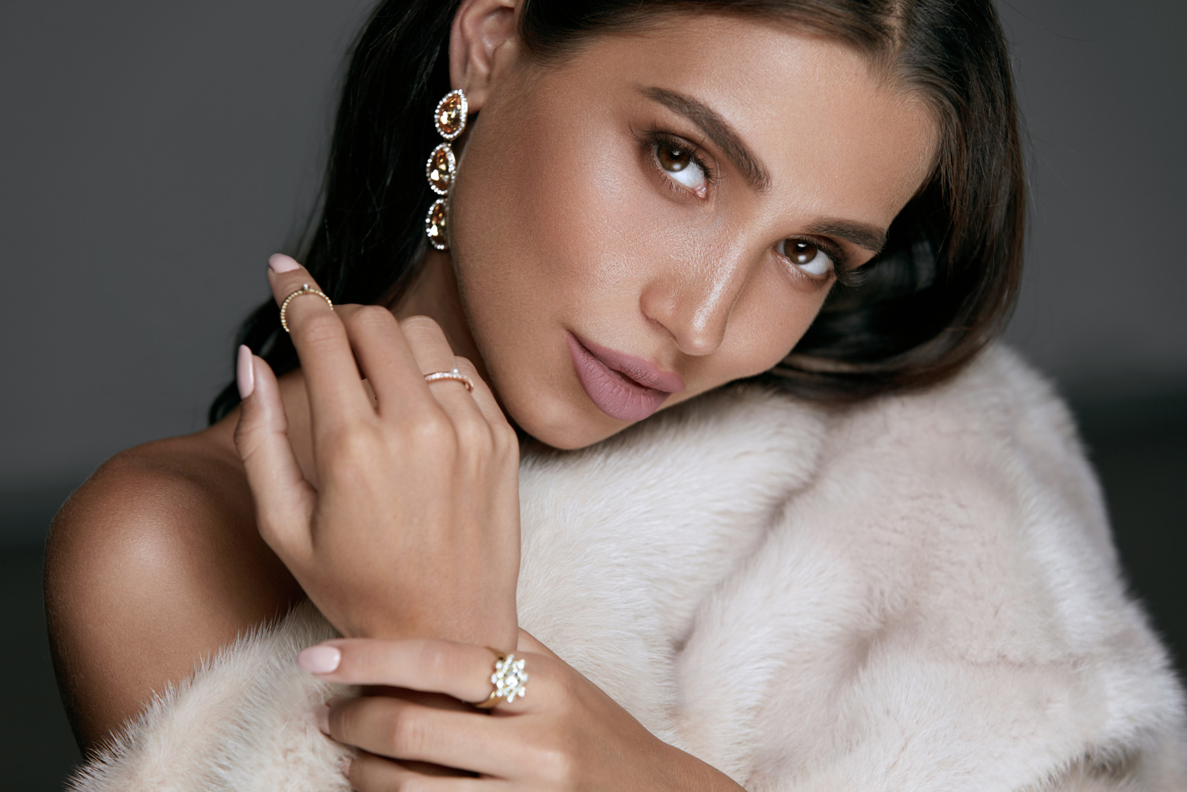A stylish young woman wearing make up and posing for a photoshoot wearing expensive jewellery