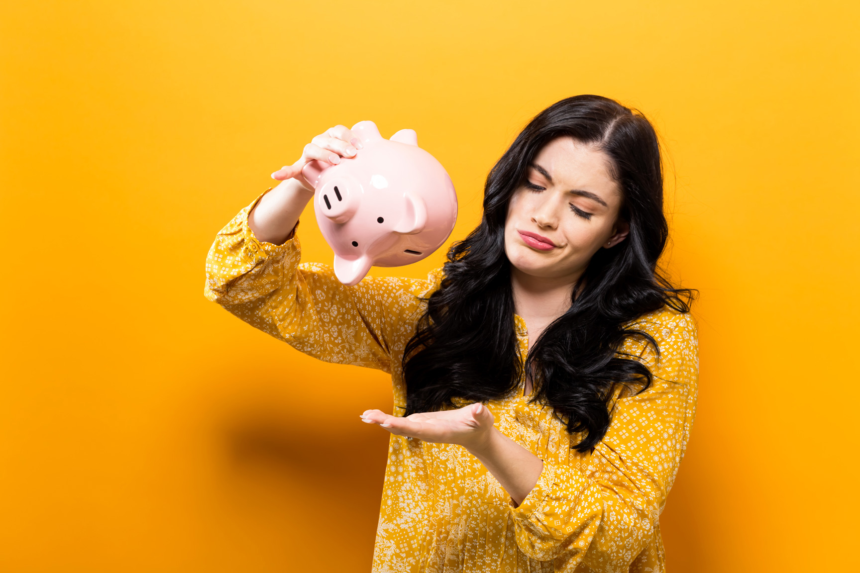 A woman holding a piggy bank upside down.