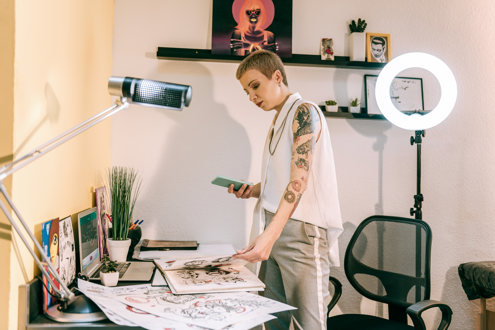 A woman having a tattoo is working in her office.