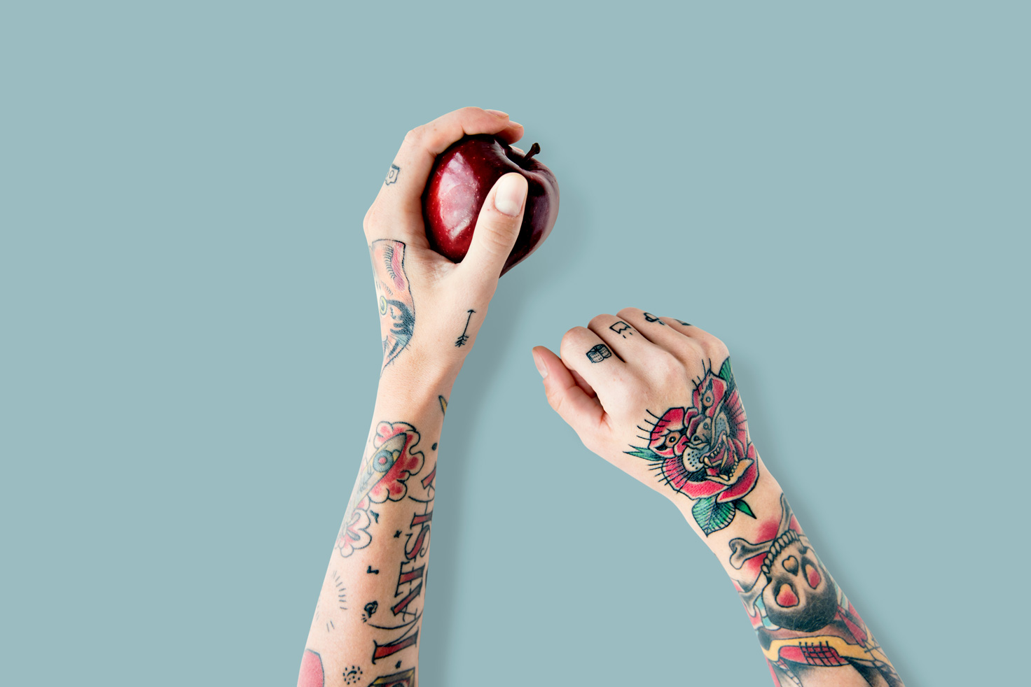 Two hands with tattoos holding an apple.